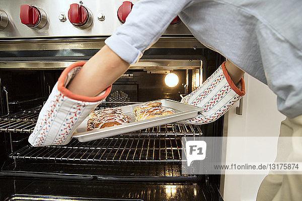 Lächelnder Junge nimmt Backblech aus dem Ofen mit dem Vater im Hintergrund