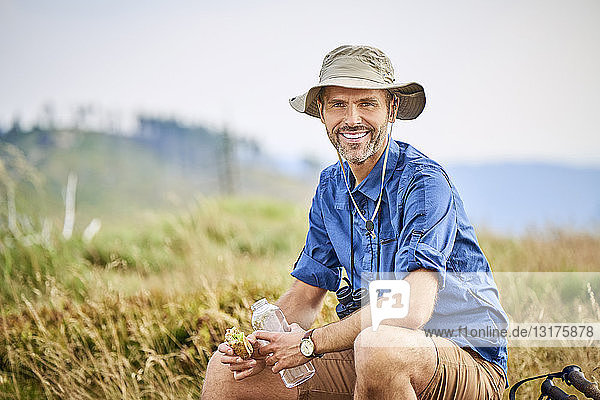 Portrait of smiling man resting and eating sandwich during hiking trip