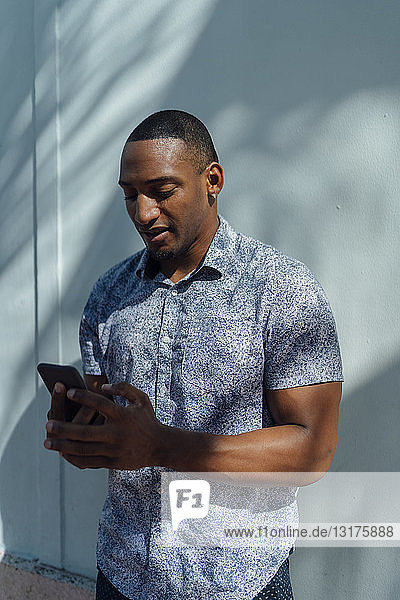 Young man wearing shirt looking at cell phone at a wall