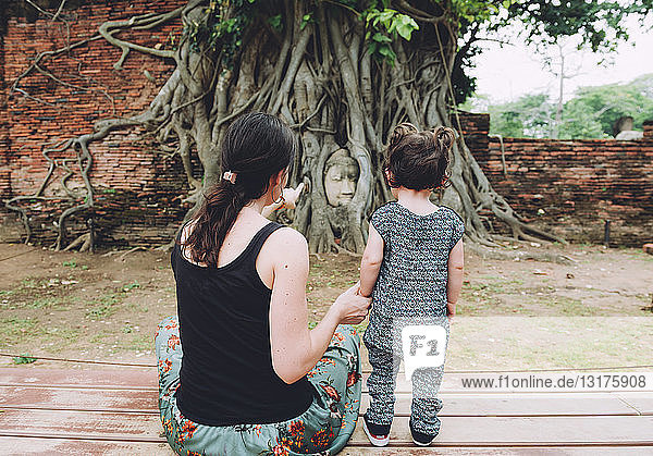Thailand  Ayutthaya  Mother and daughter visiting the Buddha head in between tree roots at Wat Mahathat