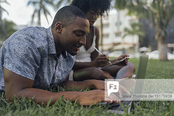 USA  Florida  Miami Beach  young couple using tablet and laptop on lawn in a park