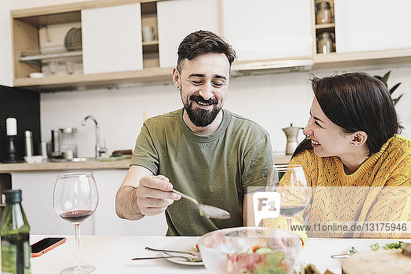 Happy couple in love having lunch together at home