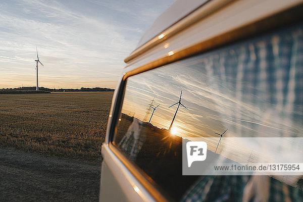 Wohnmobil in ländlicher Landschaft mit Windturbinen bei Sonnenuntergang