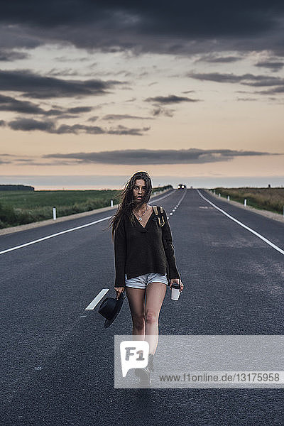 Portrait of hitchhiking young woman with backpack and beverage walking on lane at evening twilight