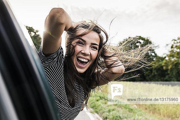 Unbeschwerte junge Frau lehnt sich aus dem Autofenster