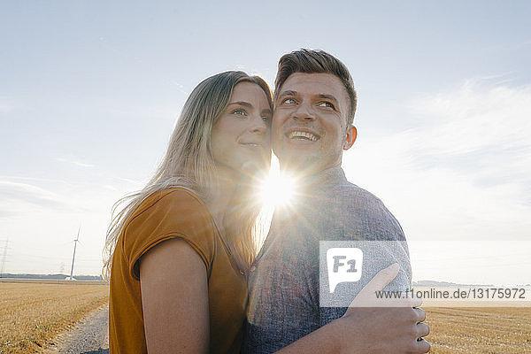 Glückliches  liebevolles junges Paar im Gegenlicht in ländlicher Landschaft