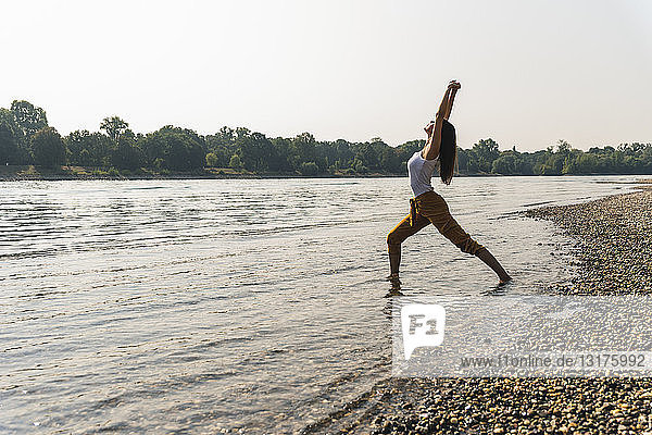 Junge Frau  die im Wasser eines Flusses steht und Yoga praktiziert