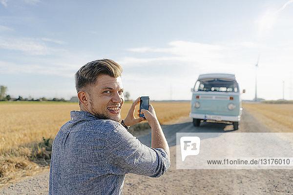 Lächelnder junger Mann beim Fotografieren eines Wohnmobils in ländlicher Umgebung mit dem Handy