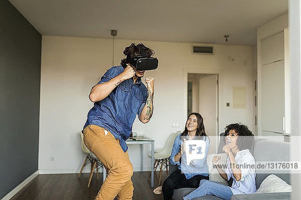 Two women encouraging man gaming with VR glasses at home