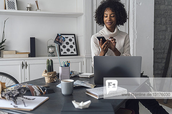 Mid adult woman working in her home office  using smartphone