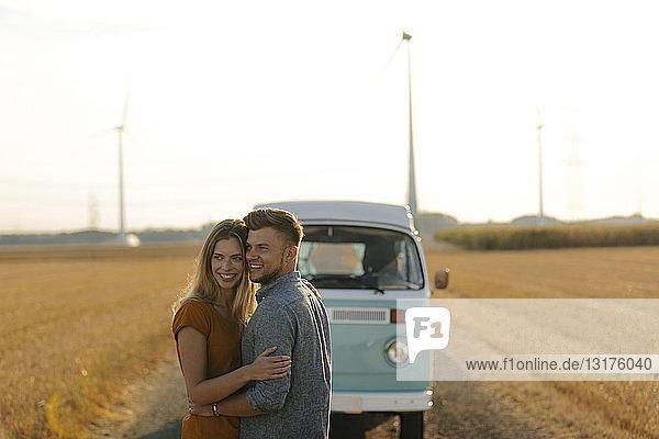 Glückliches  liebevolles junges Paar im Wohnmobil in ländlicher Landschaft
