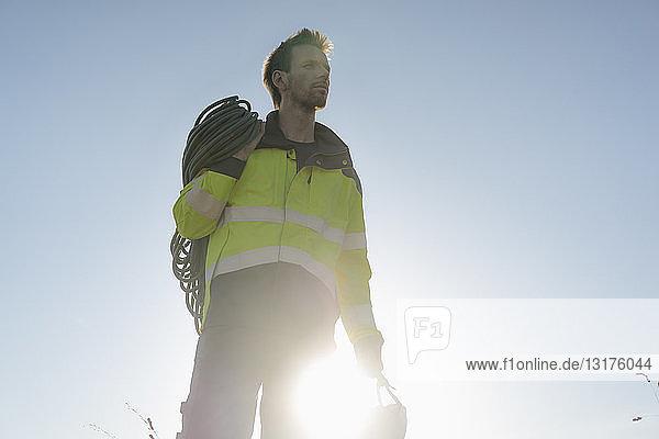 Techniker mit Kletterausrüstung unter blauem Himmel