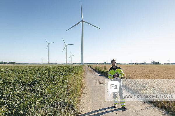 Ingenieur  der auf einem Feldweg bei einem Windpark steht