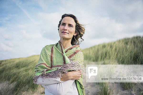 Reife Frau steht in den Dünen und schaut in die Ferne