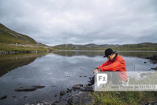 Junger Mann sitzt traurig an einem See