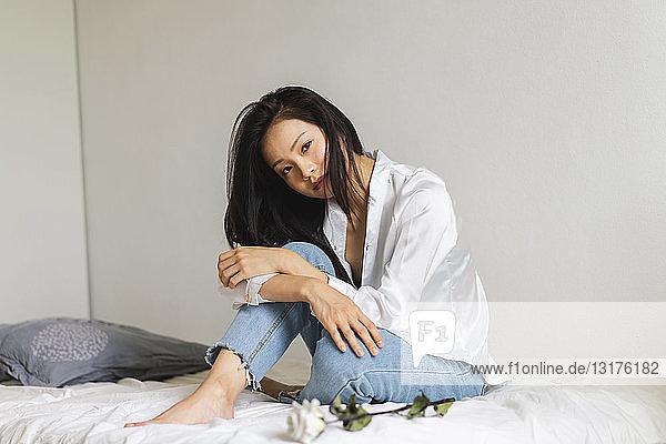Bildnis einer attraktiven jungen Frau auf Bett sitzend mit weißer Rose