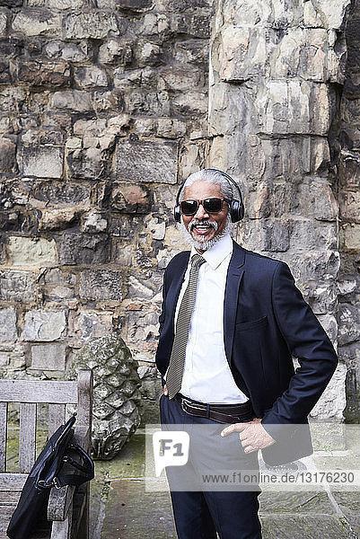 Porträt eines lachenden älteren Geschäftsmannes in Anzug und Krawatte  der mit Kopfhörern Musik hört