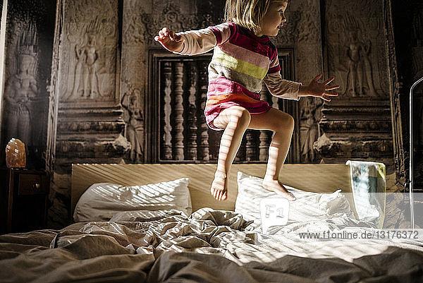 Kleines Mädchen springt zu Hause auf das Bett der Eltern
