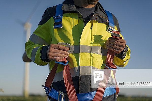 Nahaufnahme eines Technikers in einem Windpark beim Anlegen eines Klettergurtes