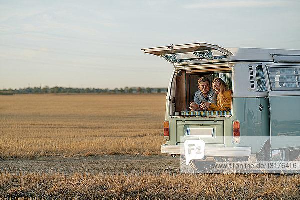 Glückliches junges Paar liegt im Wohnmobil in ländlicher Landschaft