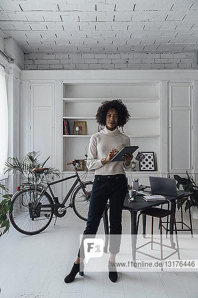 Mittlere erwachsene Freiberuflerin  die in ihrem Heimbüro steht und ein digitales Tablet verwendet