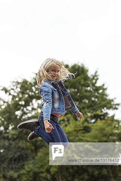 Portrait of blond girl jumping in the air