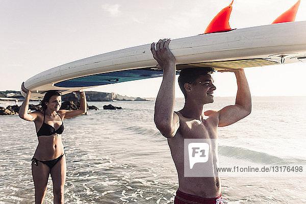 Frankreich,  Bretagne,  glückliches junges Paar mit einem SUP-Board gemeinsam auf dem Meer