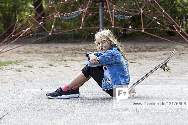 Portrait of smiling blond girl sitting with her skateboard on playground
