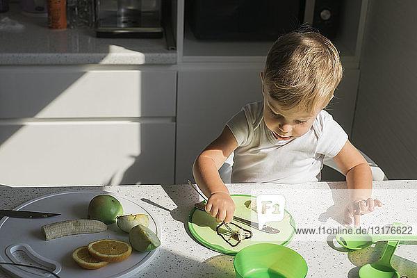 Kleiner Junge sitzt am Tisch in der Küche und isst Obst