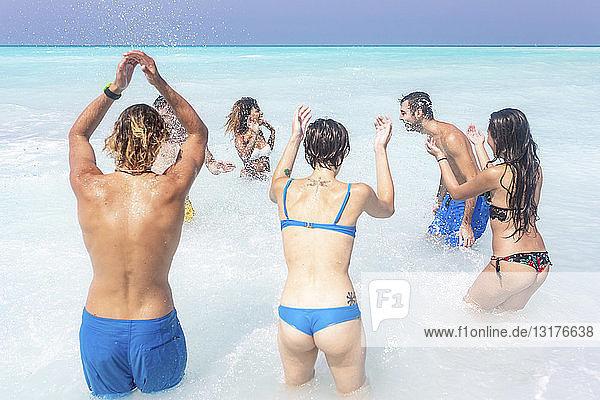 Freunde haben Spaß am Strand  springen und planschen im Meer