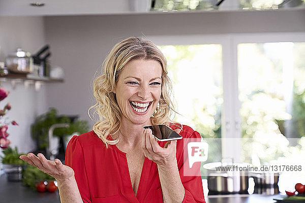 Überschwängliche Frau benutzt Smartphone in der Küche