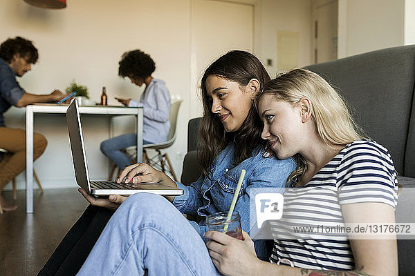 Two smiling young women sitting on floor sharing laptop with friends in background