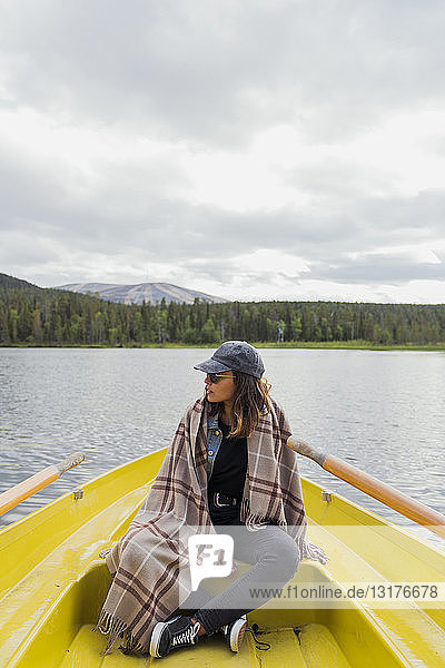 Finland  Lapland  woman wearing a blanket on a boat on a lake