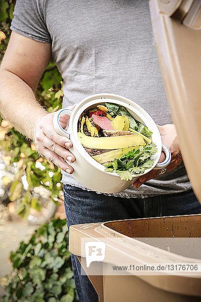 Erwachsener Mann wirft Küchenabfälle in Bioabfallbehälter Erwachsener Mann wirft Küchenabfälle in Bioabfallbehälter