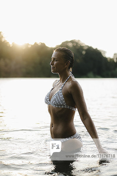 Frau trägt einen Bikini in einem See bei Sonnenuntergang
