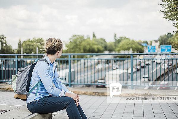 Frau mit Rucksack auf Autobahnbrücke sitzend
