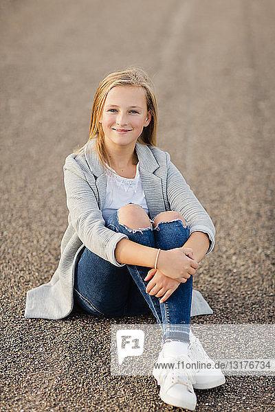 Porträt eines lächelnden Mädchens am Boden sitzend