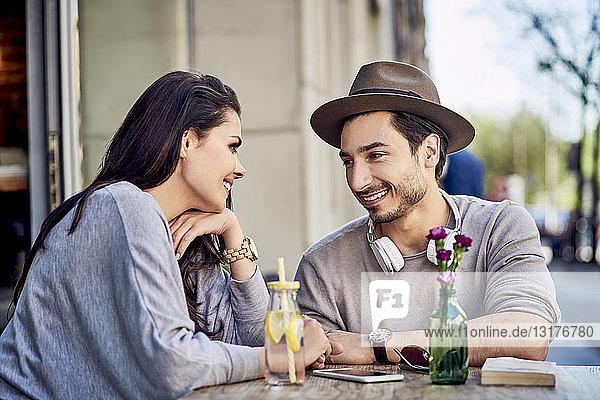 Glückliches  anhängliches junges Paar im Freiluftcafé