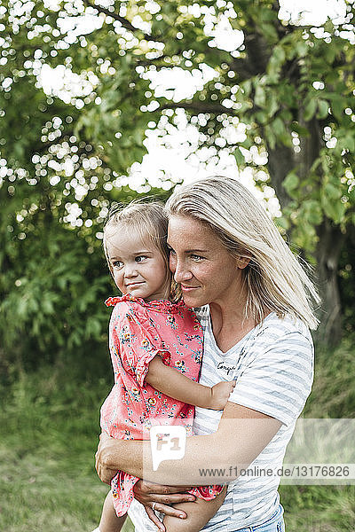 Smiling mother carrying daughter in nature