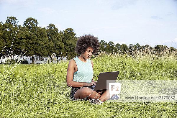 Woman sitting on meadow using laptop