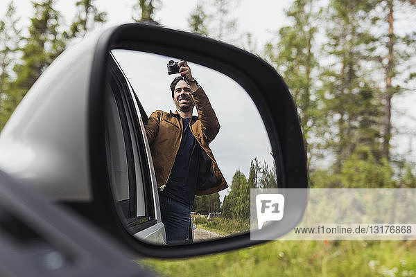 Finland  Lapland  wing mirror reflection of man taking picture out of a car