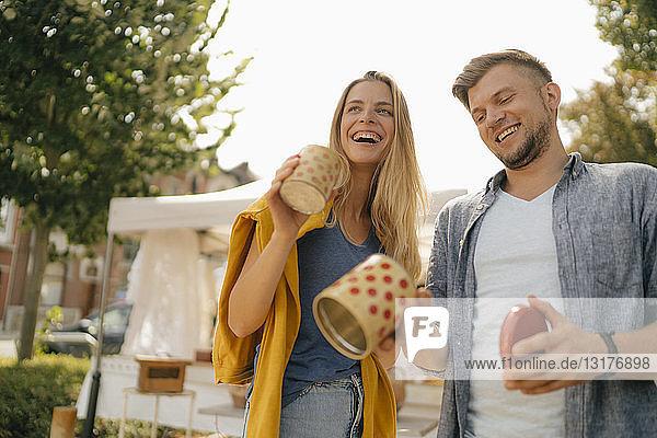 Belgien  Tongeren  glückliches junges Paar mit Blechdosen auf einem antiken Flohmarkt
