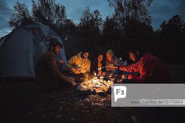 Gruppe von Freunden sitzt am Lagerfeuer und röstet Marshmallows
