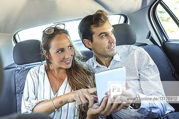 Paar mit Tablette auf dem Rücksitz eines Autos