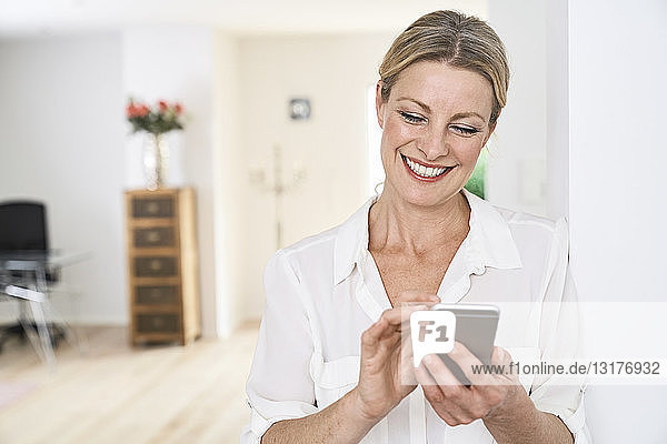 Smiling woman using cell phone at home