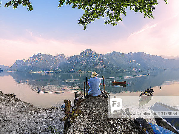 Italy  Lombardy  back view of man sitting on jetty at Lake Idro at morning twilight