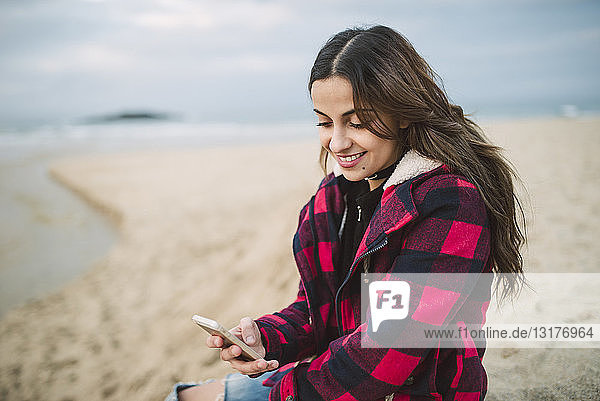 Smiling young woman using smartphone on the beach