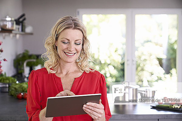 Lächelnde Frau benutzt Tablette in der Küche