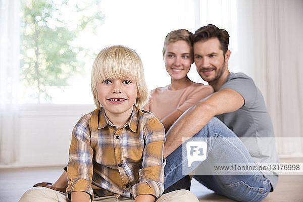 Porträt eines lächelnden Jungen mit den Eltern im Hintergrund  die zu Hause auf dem Boden sitzen