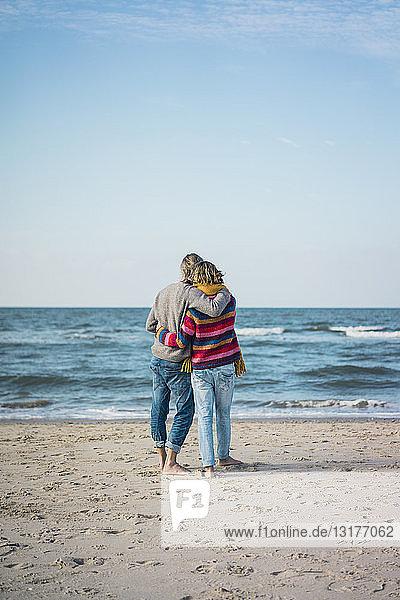 Ein Paar  das mit den Armen am Strand steht und auf das Meer schaut